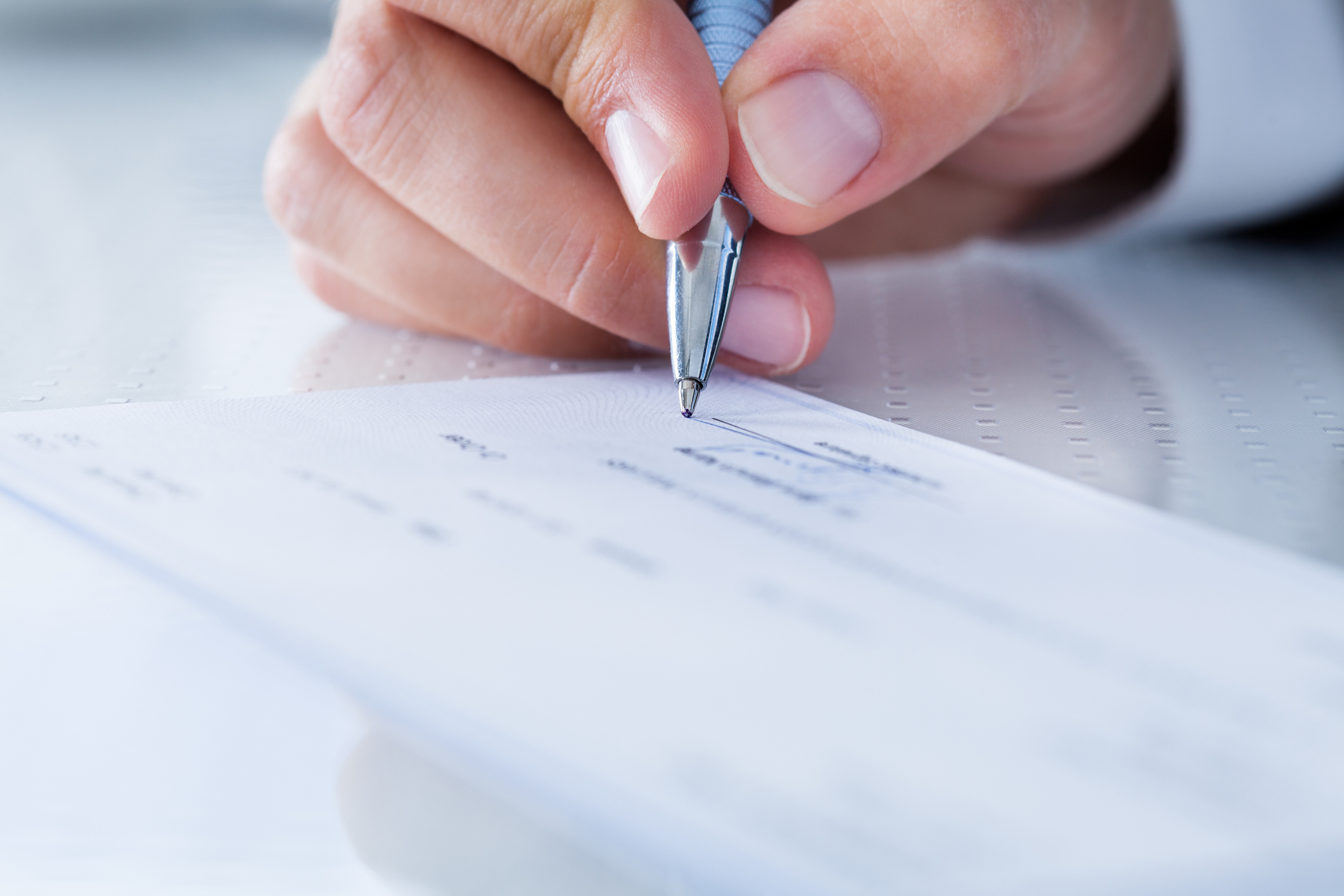 an image of a person's hand writing on a check using a shiny pen