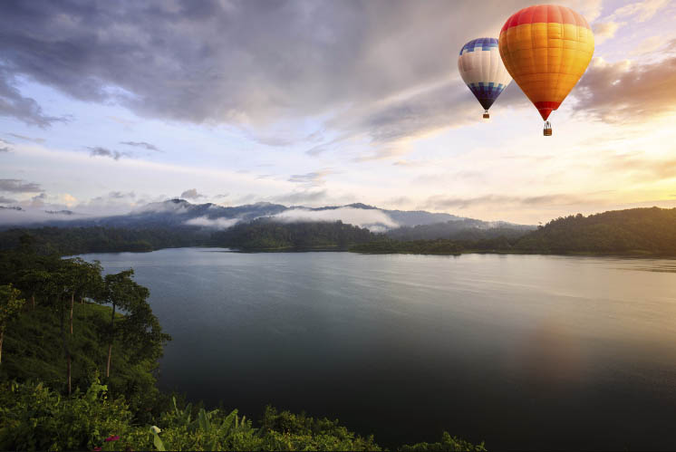 an image of two hot air balloons floating above a wide lake scenery