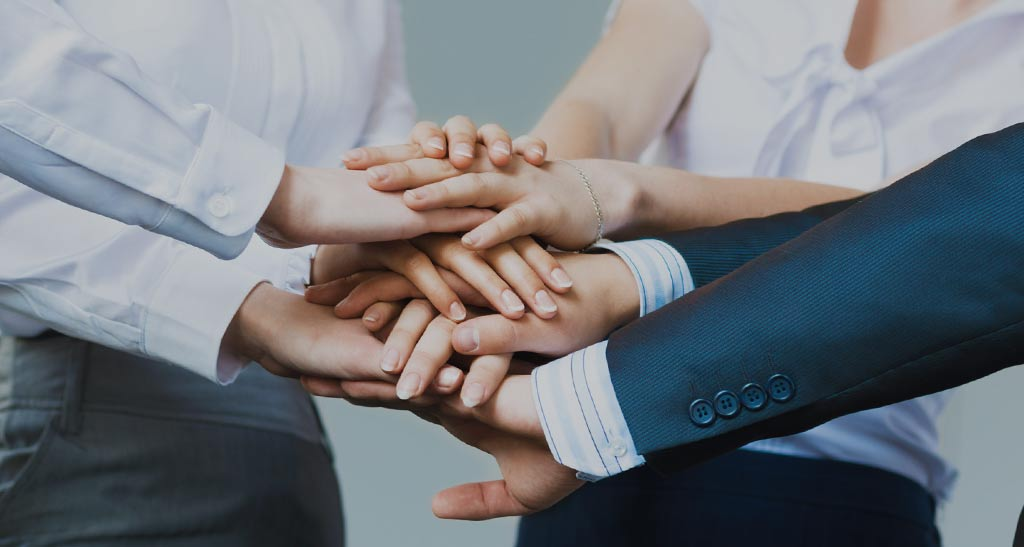 an image of a group of people stacking up their palms together