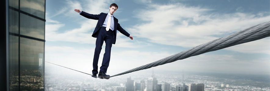 a person in a suit balancing on a wire, resembling a high risk business