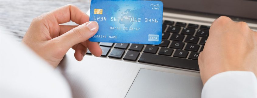 an image of a person holding up a credit card while typing on a laptop