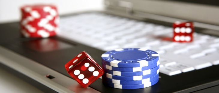an image of a laptop with two piles of casino chips and red dice